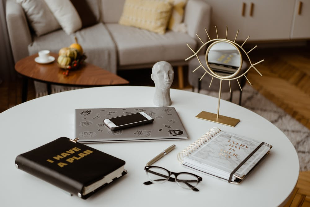 Planner, Notebook, Glasses, Laptop, Mobile Phone & Mirror On A Round Table