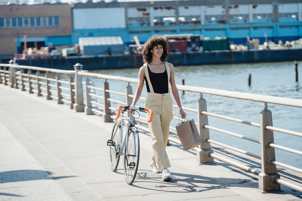 African American female with shopping bag and bicycle on seafront